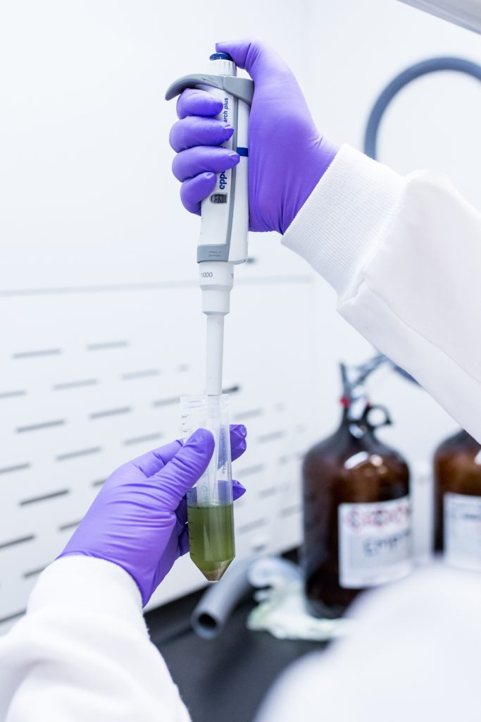 Valens Lab Technician with gloved hands holding micropipette in test tube green liquid