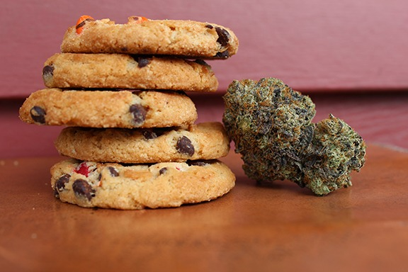 Cannabis dried bud next to a stack of chocolate chip cookies for legalization 2.0